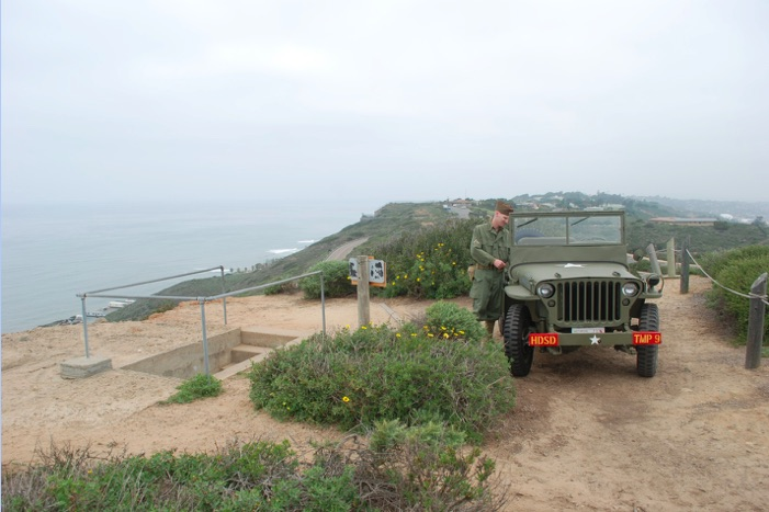 A man in world war II uniform stands next to an army jeep on a bluff, next to a set of stairs that go down into the hillside. The ocean is in the distance.