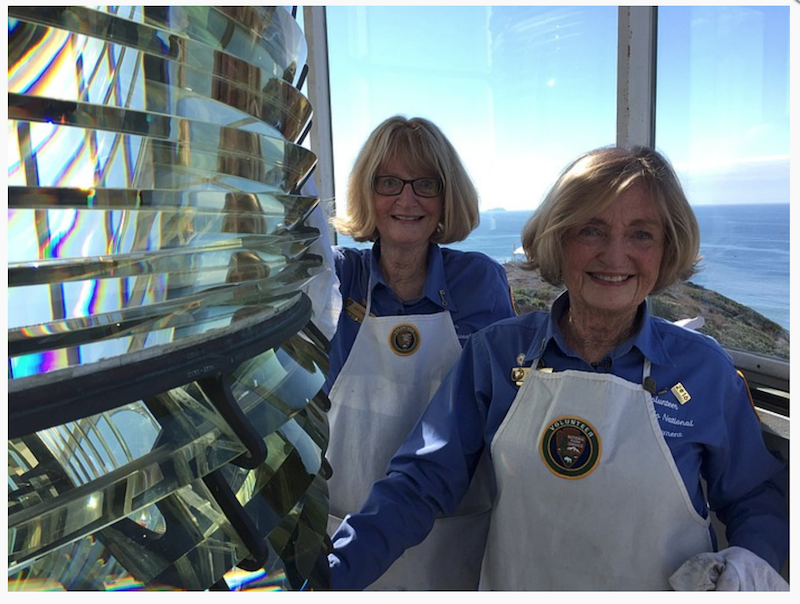 Twin sisters Kim Fahlen (left) and Karen Scanlon clean the Fresnel lens in the tower of the Old Point Loma Lighthouse, Nov. 2, 2017. (Susan Murphy/KPBS)