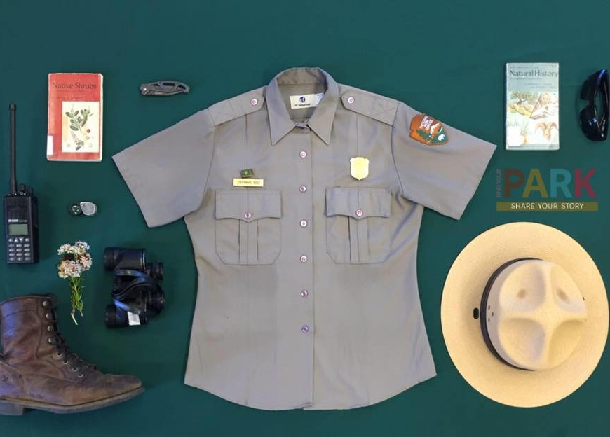 Equipment used for science field work on a green background. Equipment includes an NPS Ranger shirt, hat, sunglasses, boot, binoculars, radio, field guides and knife.