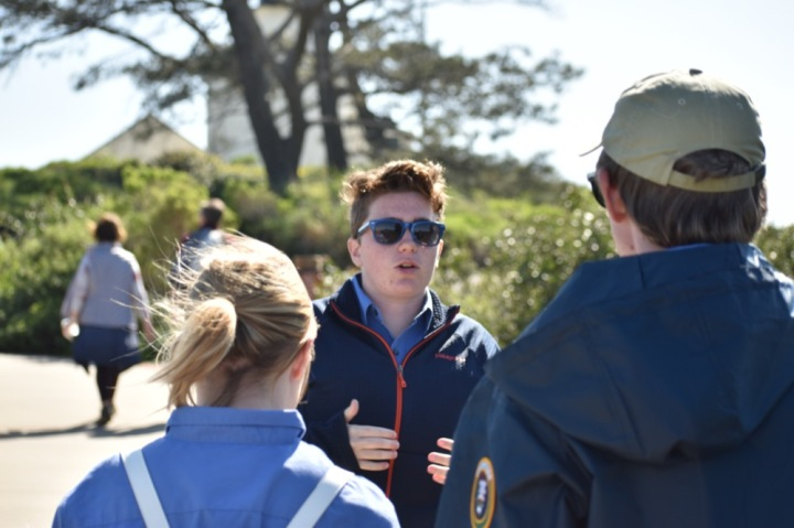 Ryan walks backwards and is engaging in conversation with two other volunteers on the trial run of this walk. In the background you can see several native trees and the Old Point Loma Lighthouse.