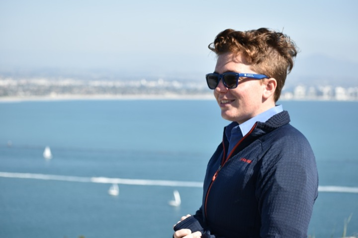 Interdisciplinary Apprentice Ryan Sullivan, wearing the light blue volunteer uniform, a navy blue jacket, and sunglasses smiles at the tour guests out of frame. The background is a blurred view of San Diego Harbor Channel and downtown San Diego.