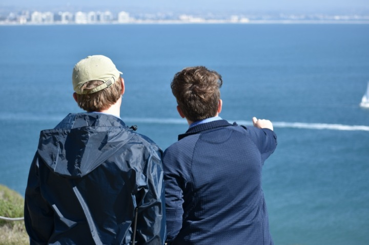 A view from the backs of Wyler and Ryan as Ryan points at something out of view across the harbor