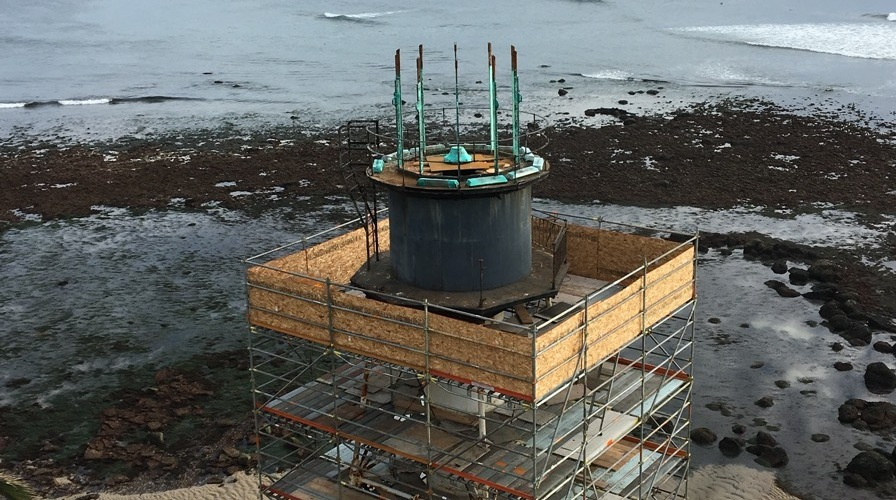 A fantastic view from a drone camera, at low tide, the lantern (top two sections of the tower) disassembly has begun. The upper lens room is now removed, leaving the barrel of the watchroom in view. (Photo by Ryan Strack.)