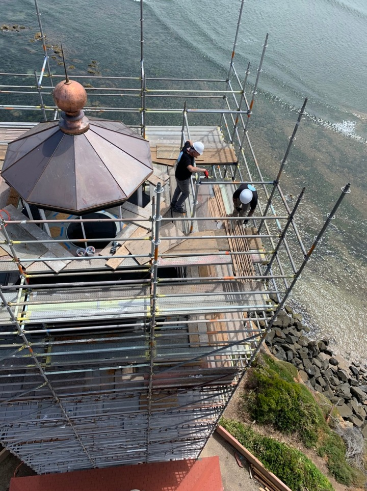 Copper roof panels, chimney and ventilator ball have been put back in place. Nick and Ryan shuffle endless components. (Photo by Kim Fahlen.)