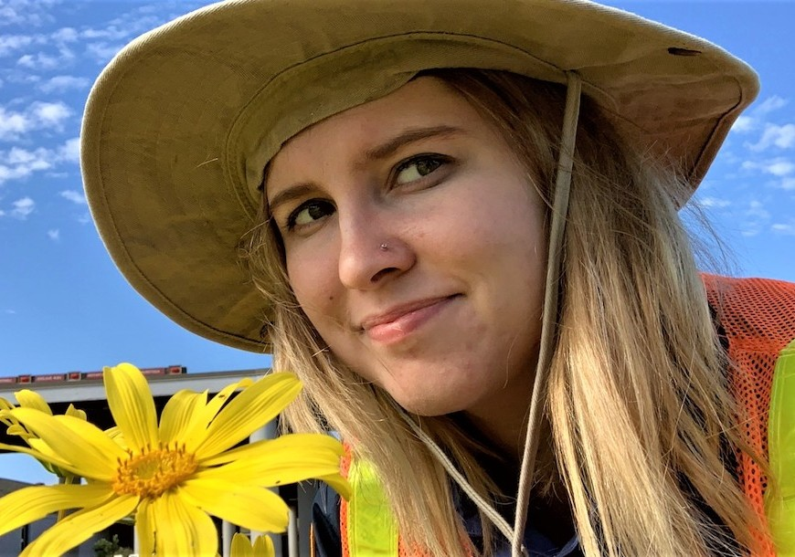 IAP Brooke Wilder admiring the spring bloom while removing invasive plants with the Weed Warriors.