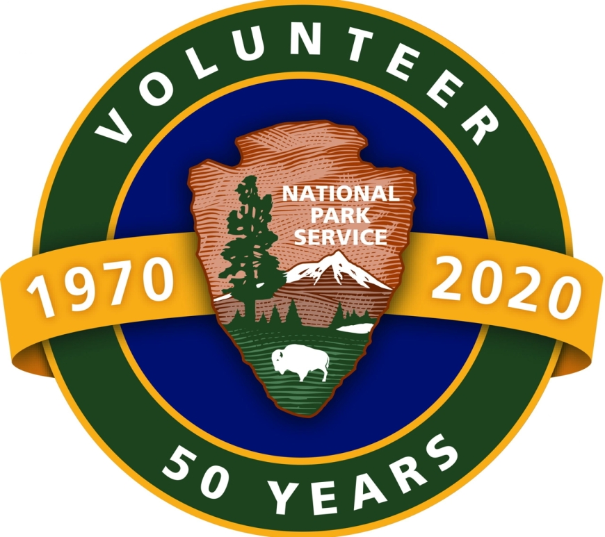 "A circular logo of the National Park Service's Volunteers-In-Parks (VIP) 50th anniversary. In the middle, a yellow banner with the years 1970 and 2020 in white font are separated by the National Park Service Arrowhead symbol in front a blue circle. A thin, yellow boundary separates the blue circle and a thicker green rim that contains the words ""Volunteer"" and ""50 years"" on the top and bottom, respectively."