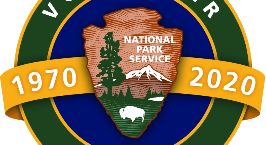 """A circular logo of the National Park Service's Volunteers-In-Parks (VIP) 50th anniversary. In the middle, a yellow banner with the years 1970 and 2020 in white font are separated by the National Park Service Arrowhead symbol in front a blue circle. A thin, yellow boundary separates the blue circle and a thicker green rim that contains the words """"Volunteer"""" and """"50 years"""" on the top and bottom, respectively."""