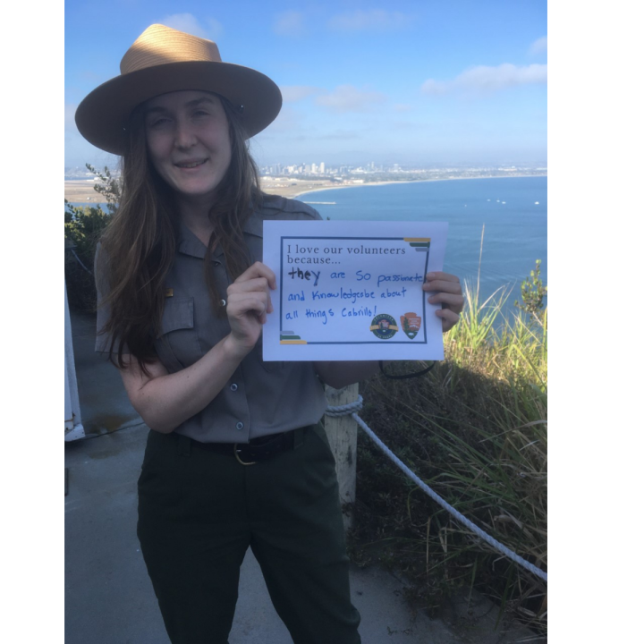 """An up-close woman with a Park Ranger uniform smiles in the shade outside in front of the San Diego Bay and skyline and holds up a sign that says, """"I love our volunteers because…they are so passionate and knowledgeable about all things Cabrillo!"""""""