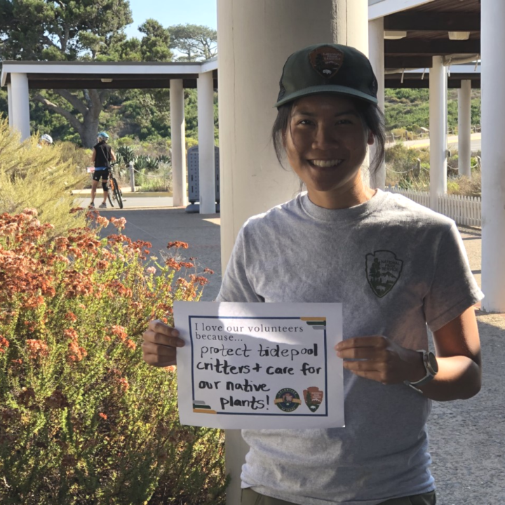 "An up-close woman with a NPS gray T-shirt and green hat smiles outside in a breezeway and holds up a sign that says, ""I love our volunteers because…[they] protect tidepool critters and care for our native plants!"""