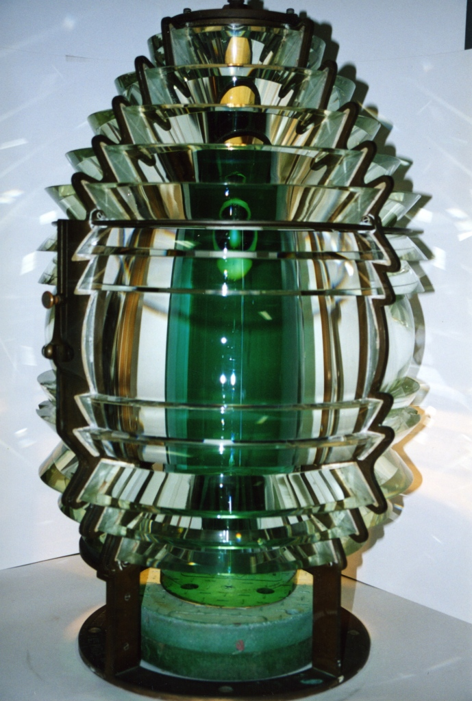 A large cylindrical light with a green center made from many pieces of small glass in different orientations focusing the beam of light.