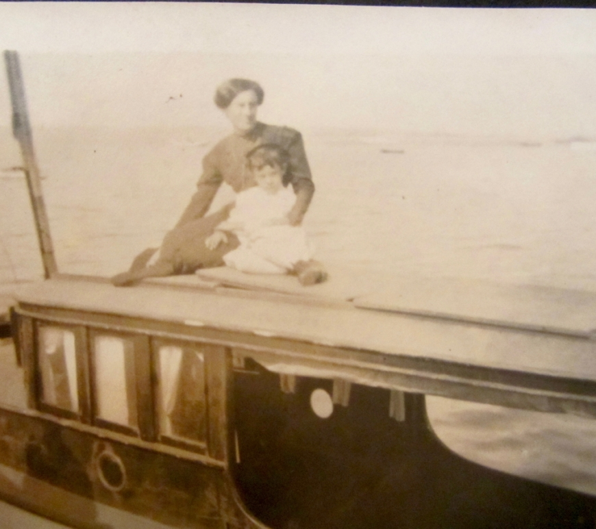 Celia Sweet wearing a dark dress standing behind her daughter Verla in a white dress sitting on top of a roof aboard her boat, Relue with water behind them.