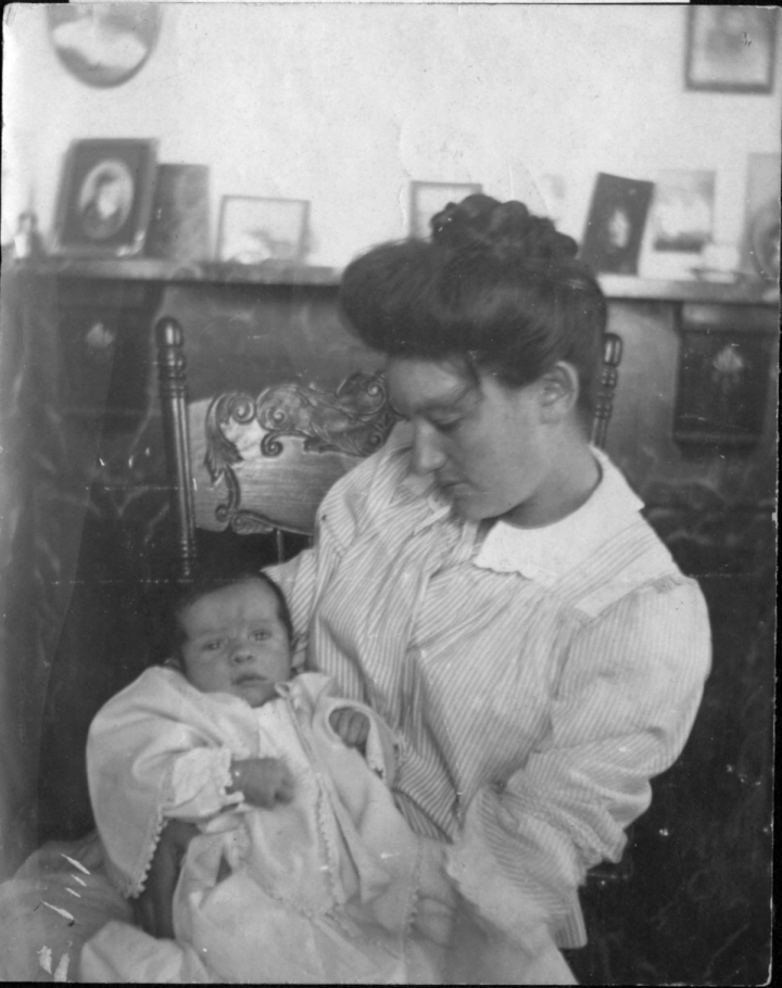 Celia Sweet wearing a long sleeved light colored dress holding baby Alton in her arms in a room in the lighthouse.