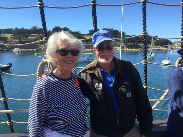 Iris Engstrand wearing a blue and white horizontally striped shirt standing next to Ray Ashley wearing a blue cap. They are standing on the bow of a ship.