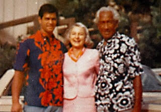 "Miss Billy Riley in a pink dress standing between Kimo McVay wearing a colorful blue shirt with orange flowers and The Duke"" Kahanomoku wearing a blue with white flowers Hawaiian shirt."