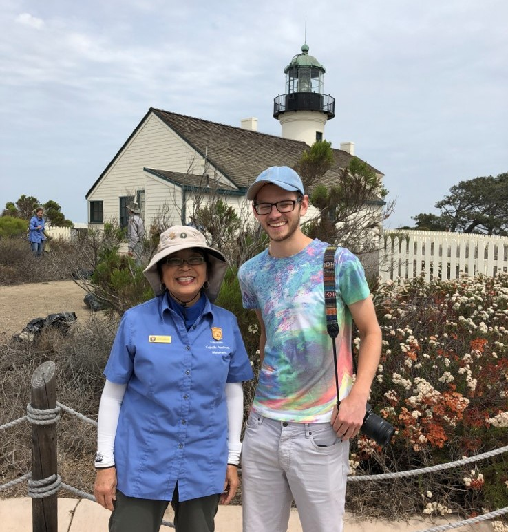 A woman in a blue shirt and sun hat stands next to a man in a tie dye shirt and blue baseball cap in front of a lighthouse.