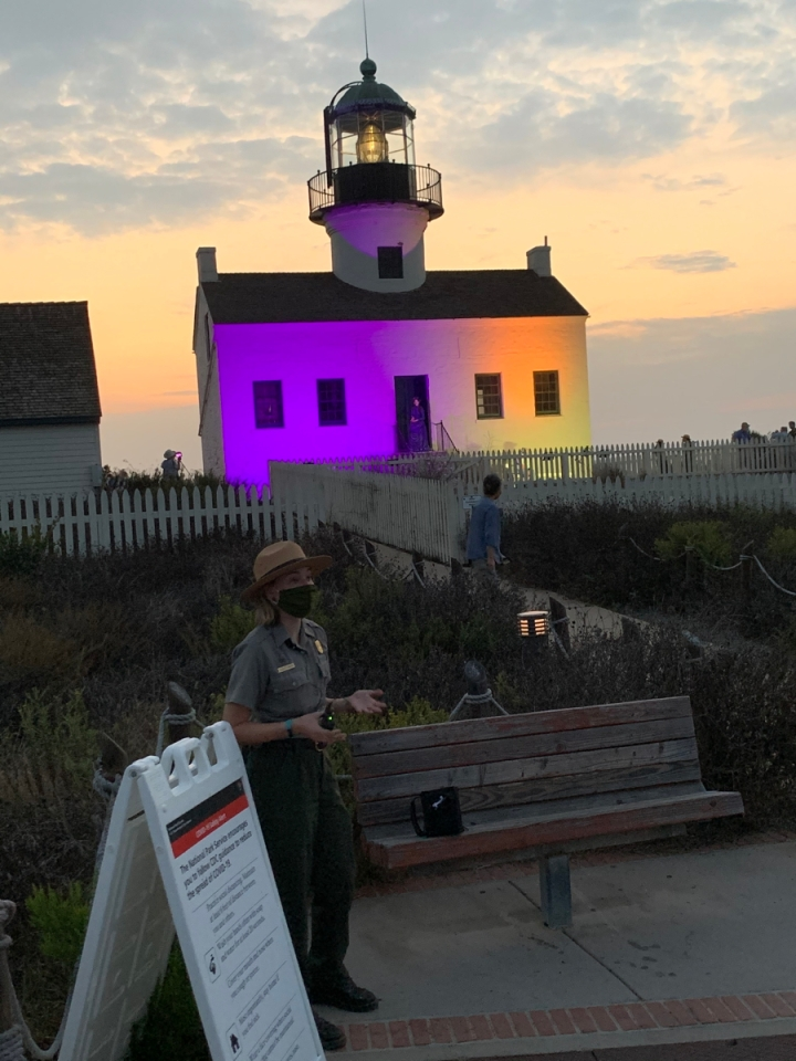 Lighthouse at night lit up with purple and gold. A ranger stands in the foreground by a sign talking to visitors.