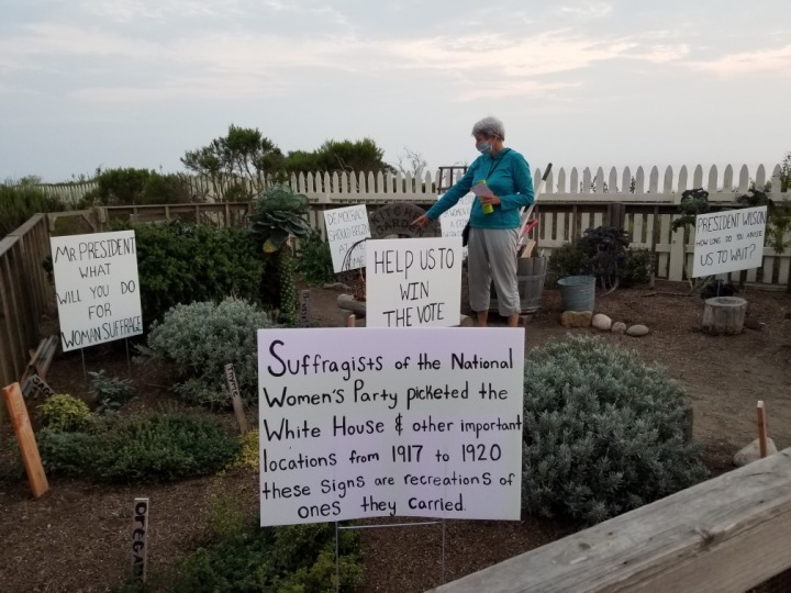 A woman stands in a garden with picket signs.