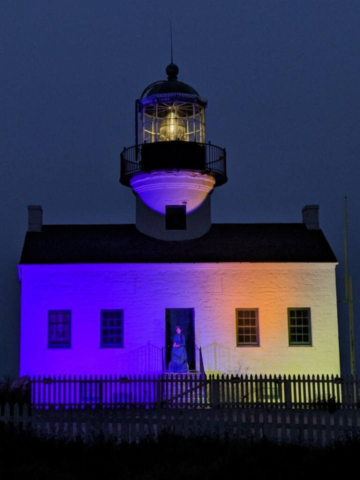 Lighthouse at night lit up with purple and gold.