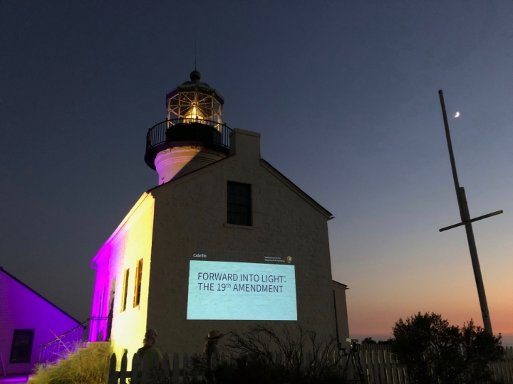 Lighthouse at night lit up with purple and gold with slideshow displayed on side of building. A flagpole with the moon above it is to the right of the building.