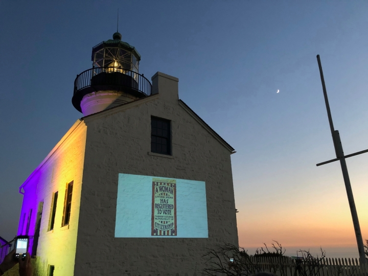 Lighthouse at night lit up with purple and gold with slideshow displayed on side of building. A flagpole is to the right with the moon above it.