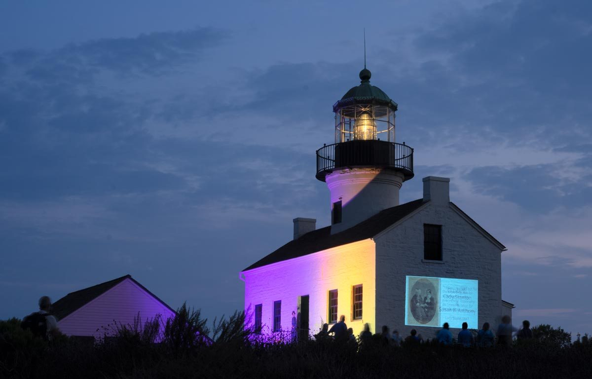 Lighthouse at night lit up with purple and gold with slideshow displayed on side of building.