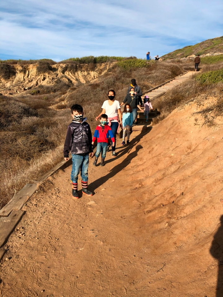 Family wearing face masks walking along dirt trail