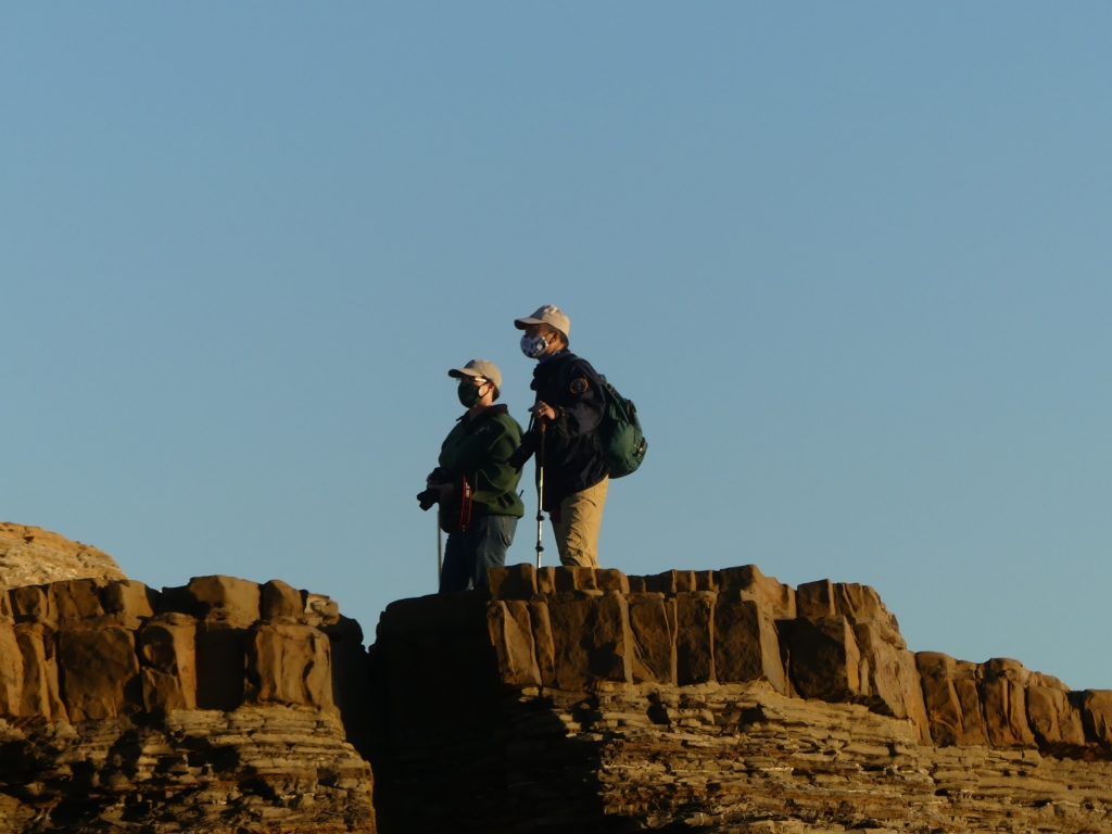 Volunteers in baseball caps and jackets stand on sandstone cliffs.