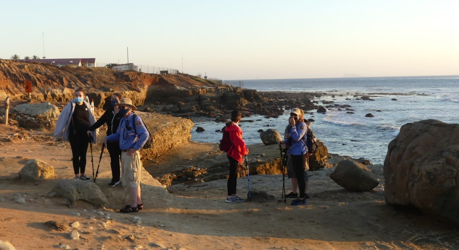 People stand on sandstone cliffs overlooking the ocean. Volunteers are wearing long sleeve blue shirts.