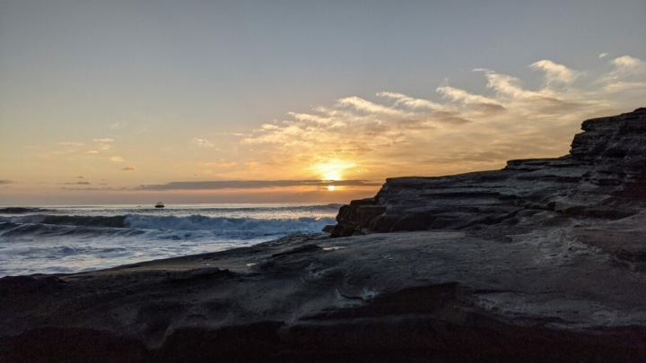 Sunset view of ocean and sandstone cliffs