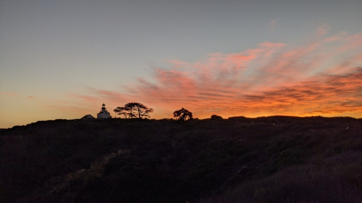 Panoramic orange sky at sunset with lighthouse and trees in shadow