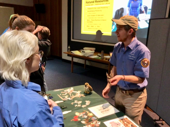 Park volunteer Wyler stands behind a green table in the park auditorium and holds a brown rubber mold of a bird's feet and interacts with other park VIPs during a Science Explorer's Club training. Another VIP and staff member interact separately and away from the camera, and a projector screen shows content about the Science Explorer's club.