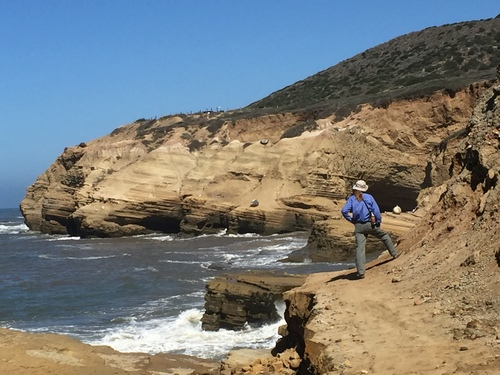 A shot from behind as a volunteer stands on a sandstone cliff at the tidepool area. The hillside turns upward sharply to her right. To the left the cliff drops off into the turbulent waters of the ocean.
