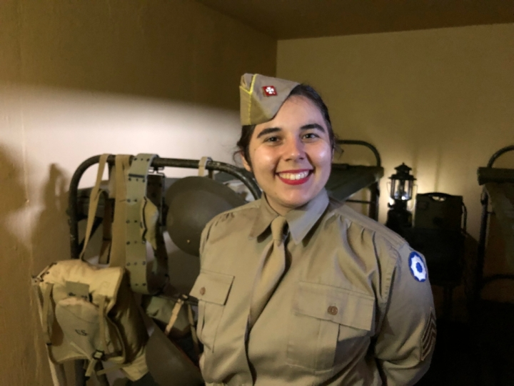 WWII volunteer Stephanie stands smiling in the dimly lit lower portion of battery bunker E. Stephanie is dressed in a drab colored long sleeve shirt with a similar colored hat. A bunkbed is behind her, strewn with WWII armor and ammunition.