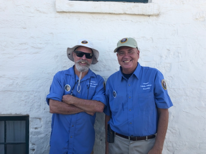 VIPs Craig (left) and Mike (right) smile and stand directly in front of a side of the Old Point Loma Lighthouse during an Open Tower Day event.