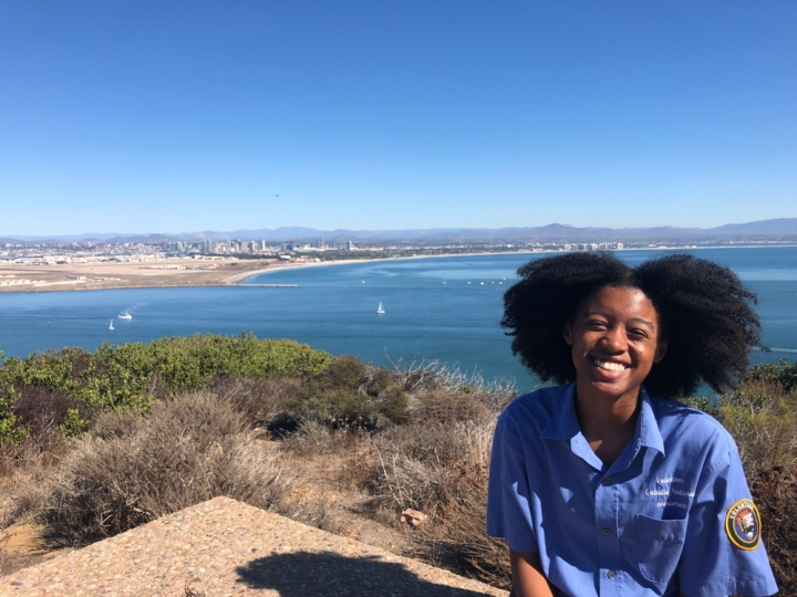 VIP Felix sits on a seating area behind the Visitor Center and smiles at the camera. Behind her are various green-and-gray plants, the San Diego bay containing a few white sailboats and ships, the San Diego skyline, and mountain ranges, all under a blue cloudless sky.