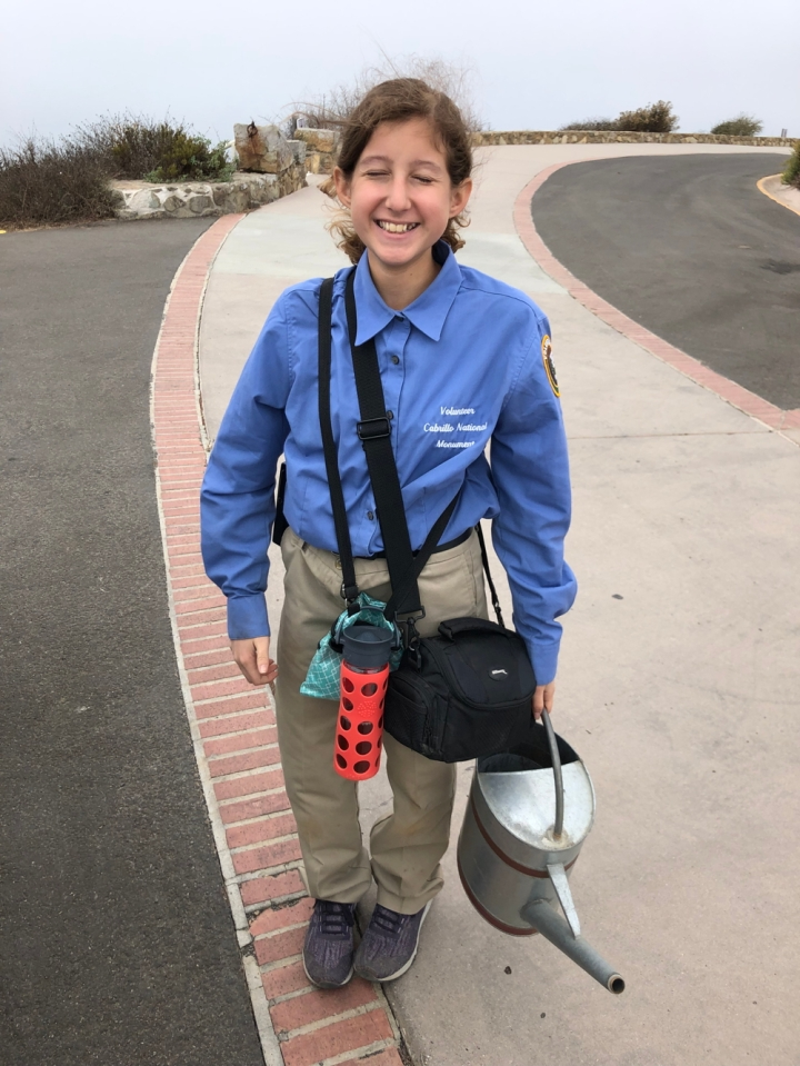VIP Violette stands on a paved road behind the Old Point Loma Lighthouse with eyes closed and carrying a metal watering can, a photo camera, and a water bottle.