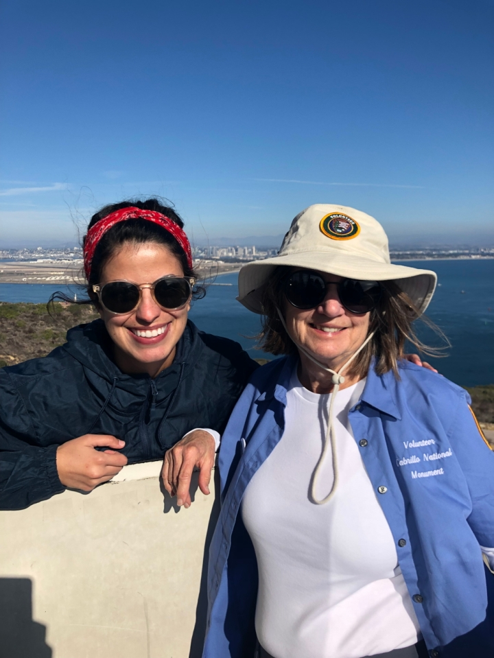 CVA Setareh, behind a short and white wall, and VIP Gayle stand on top of the Old Point Loma Lighthouse's catwalk and smile at the camera. Behind them is a very small Cabrillo statue atop a hill, the San Diego bay and skyline, and mountain ranges.