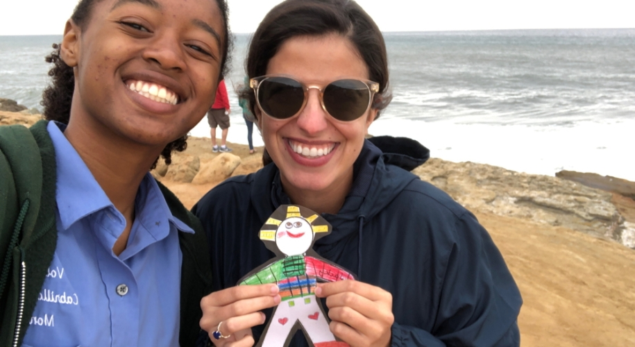 Park volunteer Felix wears an unzipped dark-green jacket and stands on a cliff next to CVA Setareh, who is wearing a zipped navy-blue windbreaker with sunglasses and holding a colorful Flat Stanley cutout. Both Felix and Setareh are smiling at the camera and facing away from the ocean. Two people stand at the edge of the cliffs behind Setareh and Felix, with their faces away from the camera.