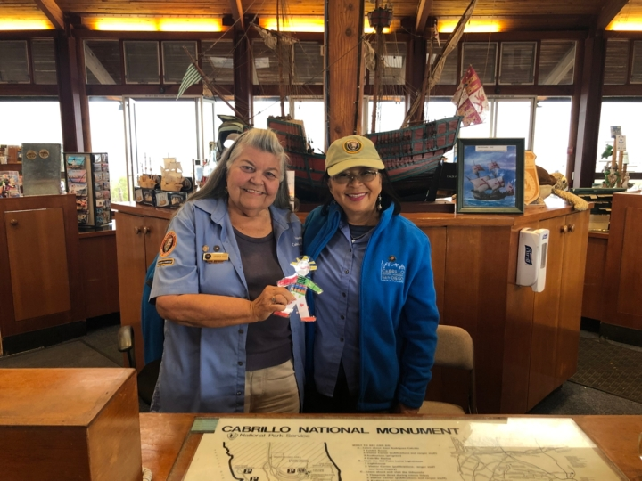 Smiling volunteers Barbara and Romi stand side-by-side behind a desk in the Visitor Center. They hold up a laminated, hand-drawn, colorful paper doll. Behind them is a replica of Cabrillo's sailing ship, the San Salvador.