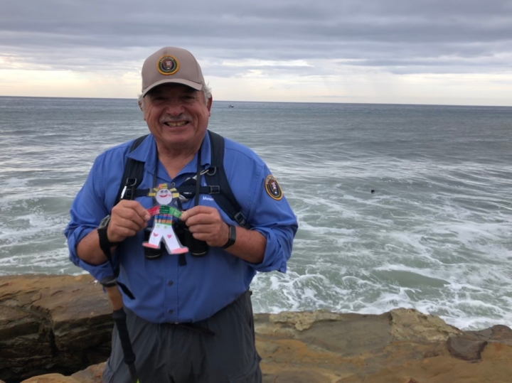 Volunteer Alan stands smiling on a sandstone cliff at the edge of the sea. He holds up a laminated, hand-drawn, colorful paper doll.
