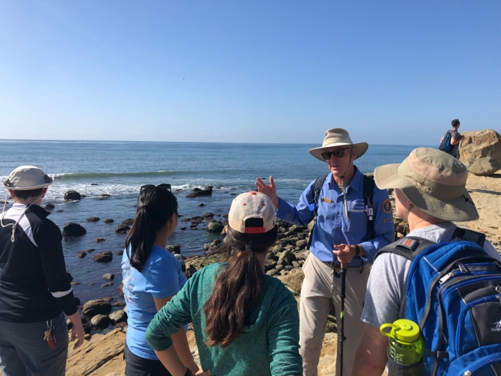 VIP Bob stands in the rocks in Cabrillo's tidepools and speaks to four visitors with cresting waves and ocean behind him.