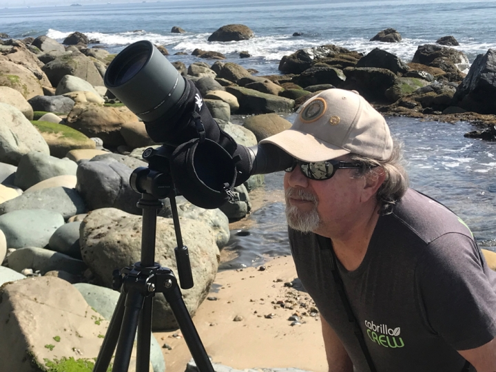 VIP Bob stoops to look through a large spotting scope that is nestled amongst rocks and water in the tidepools. The expanse of the ocean stretches behind him.