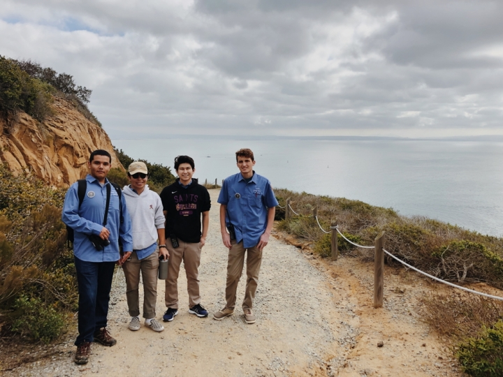 From left to right, park apprentices Alberto, Jackson, Christopher, and Eric stand side-by-side at the Bayside Trail and smile at the camera, with their backs to the ocean and overcast sky. Alberto and Eric wear park binoculars, and Jackson and Christopher wear hoodies that cover up their light-blue volunteer uniforms