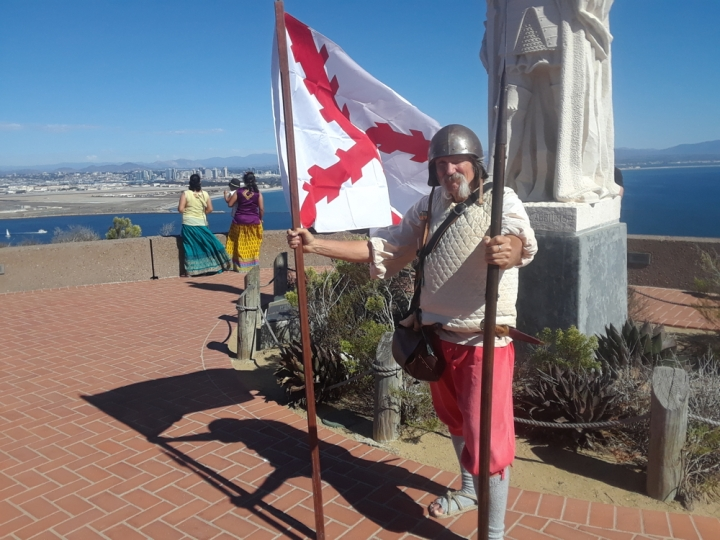VIP Gary stands in front of the Cabrillo statue and holds a white flag with red lines in one hand and a spear in the other. He is dressed in 16th century Spanish soldier garb: a metal helmet, a thick white vest, short red pants, long gray socks, and tan woven sandals.