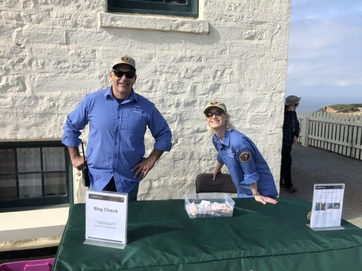 Volunteers Nick and Lizzie stand outside in front of a white building behind a green table with a sign that says Bag Check.