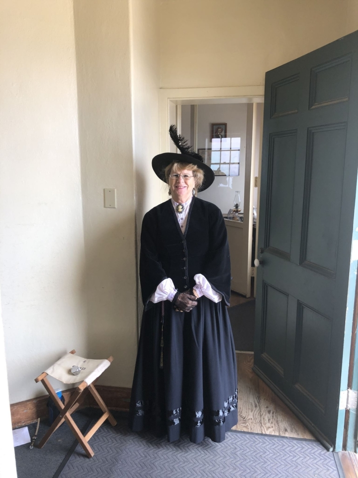 The large green front door of the lighthouse opens into the white foyer. Vicki, a volunteer stands inside the foyer ready to greet visitors wearing a dark blue dress and hat from the 19th century.