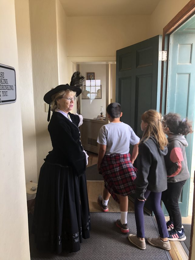 The large green front door of the lighthouse opens into the white foyer. Vicki, a volunteer stands inside the foyer ready to greet visitors wearing a dark blue dress and hat from the 19th century. Three children enter the lighthouse and head towards the room in the back of the photo.