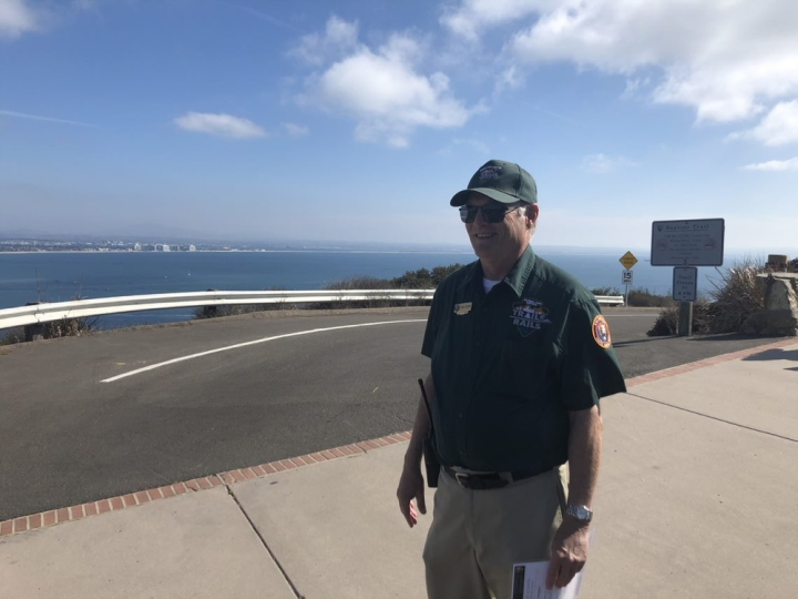 Mark, a volunteer wearing a dark green shirt and hat, stands smiling at the intersection of two paths. Beyond the road behind him is the shimmering blue waters of the bay, and beyond that are the sandy shores of the silver strand isthmus.