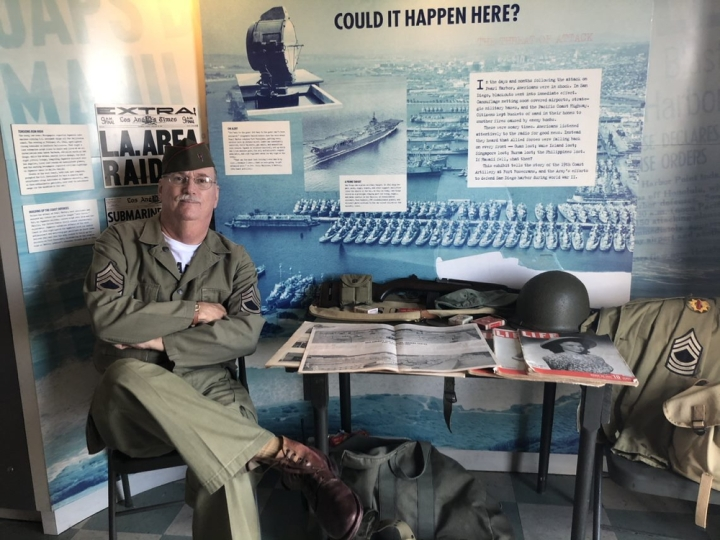 Tim, A WWII military history volunteer sits inside the military history exhibit; arms and legs crossed wearing an olive colored military uniform with a dark green hat and brown shiny boots. There is a table to his left with military helmets and publications from the 1940s.
