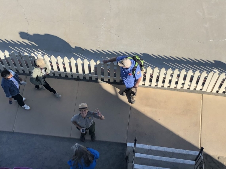 A view looking down from the top of the lighthouse to the entrance below. Ranger Amanda stands smiling up at the photographer while flashing a peace sign. Two volunteers, Barbara and Larry, stand ready to greet two visitors.